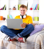 Young man relaxing on sofa with  laptop