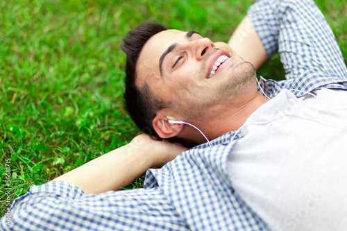 Young man listening to music lying on the grass