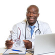 African doctor on a desk with glasses in his hand