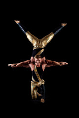 Smiling muscular acrobats isolated on black
