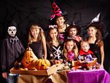 Children on Halloween party making pumpkin