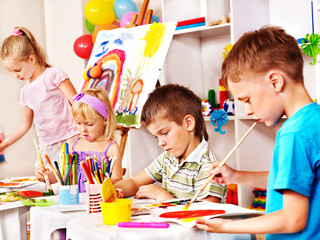 Children painting at easel.