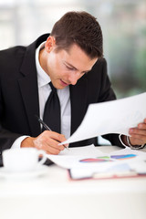 businessman writing at his desk