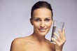 Beautiful smiling woman holding a glass of pure water