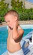Young boy applying suntan lotion