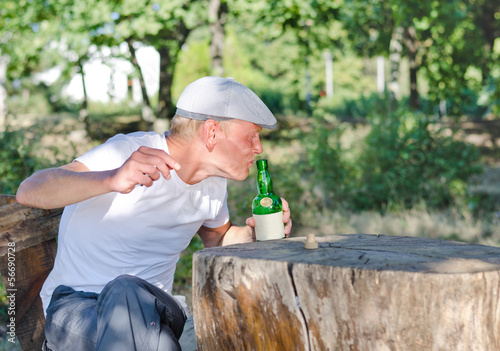 Man taking a swig of alcohol from a bottle