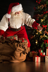 Santa putting gifts under Christmas tree in dark room