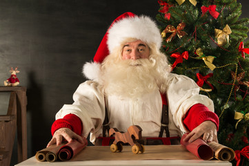 Santa Claus working - preparing and wrapping christmas gifts