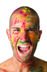 Young man screaming with face's skin painted with colors