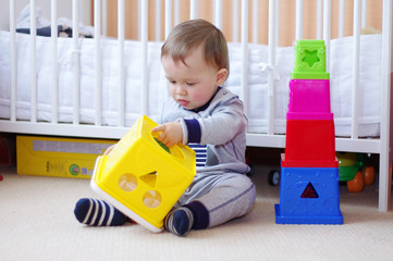 baby boy age of 1 year plays nesting blocks