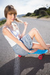 Funky young blonde sitting on her skateboard