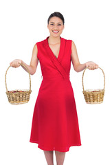 Cheerful glamorous model in red dress holding baskets