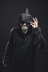 skeleton in a black robe holds sunglasses