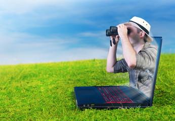 Explorer looking through binoculars from a laptop