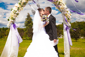 First kiss of newly married couple under wedding arch