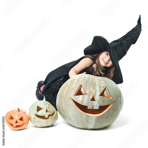little witch hiding behind pumpkins