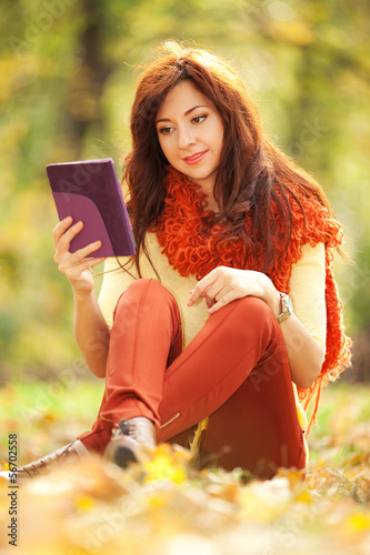 Young pretty woman with tablet  in the autumn park