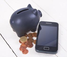 hucha, monedas y móvil