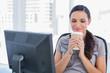 Happy attractive businesswoman holding coffee