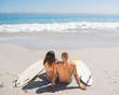 Young couple with their surfboards looking at the sea