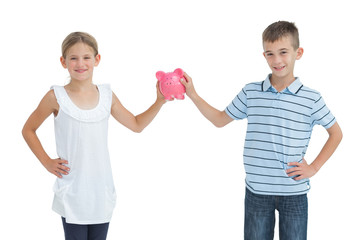 Brother and sister holding piggy bank together
