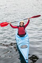 Happy woman in a kayak cheering at the camera