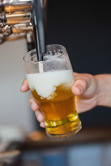 Hand holding glass filling beer