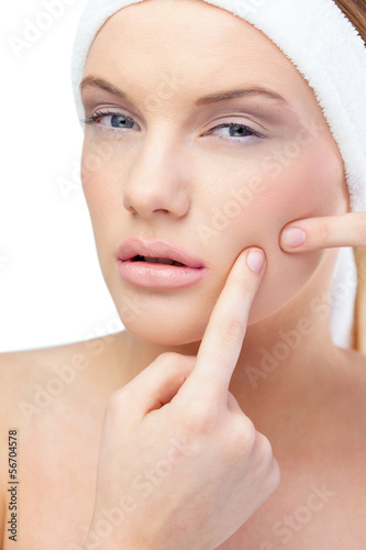 Blonde model pressing pimple on her cheek
