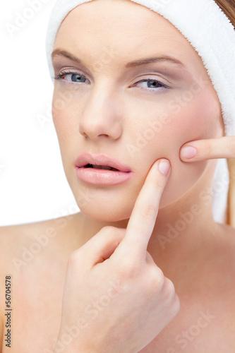 Blonde model pressing pimple on her cheek