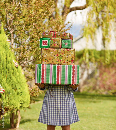 Girl holding pile of Christmas presents