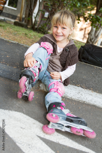 Cheerful roller skater - child girl - in protective equipment si