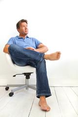 Mann auf einem weißen Bürostuhl sitzend