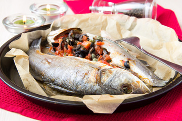 Baked whole white fish, sea bass stuffed with tomato, olives
