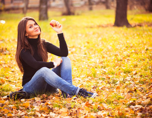 Portrait of beautiful young woman with apple in autumn park