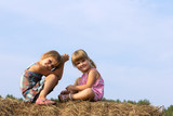 Two girls sit on haystack