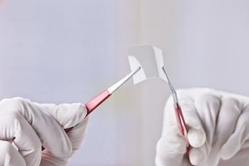 Hands of scientific showing a piece of graphene.