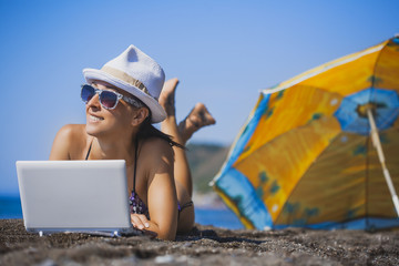happy smiling girl is sunbathing with laptop