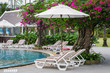 couches with umbrellas around the pool