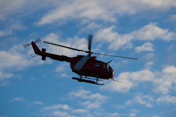 Red and white helicopter against nice sky