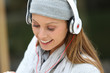 Trendy young woman in park listening to music