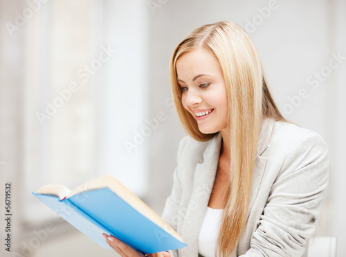 young woman reading book at school