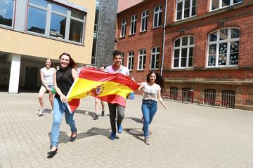 Schüler mit spanischer Flagge laufen