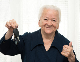 Senior woman with a car key and making OK gesture