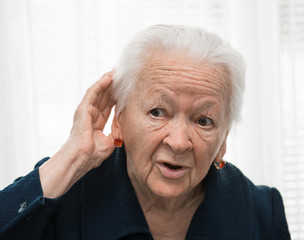 old woman putting hand to her ear. Bad hearing