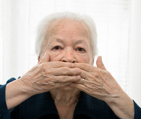 Senior woman holding hands over mouth