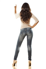 young woman in jeans with her finger touching imaginary object