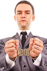 Closeup portrait of a young businessman with handcuffed hands