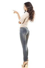 side view of young woman in jeans touching imaginary object