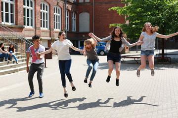 fröhliche Schüler springen draußen