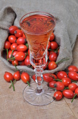 Rosehip fruit and alcoholic liquor in a glass